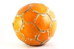 Worn orange soccer ball Stock Photos