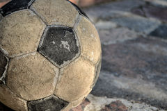 Worn-out ball, too much football. A worn-out ball used by kids to play football Royalty Free Stock Images
