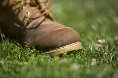 Worn out boots. Close up of the sole of a damp muddy and worn out boot with loose laces on grass, with focus on the toe Stock Photos