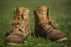 Worn out boots. Damp muddy and worn out boots with loose laces on grass Stock Image