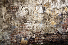 Worn out brick wall. An image of a worn out brick wall with its plaster badly damaged from exposure to the element royalty free stock images