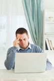 Worn out businessman on his laptop. Worn out young businessman on his laptop Stock Photo