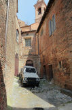 Worn out car parked in an old town, Umbria, Italy Royalty Free Stock Photos
