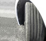 Worn Out and Damaged Car Tire. Badly worn out car tire tread and damaged bulb like side due to wear and tear or because of poor tracking or alignment of the stock image