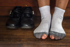 Worn out dirty  socks with a hole and toes sticking out  of them on  old wooden floor. Stock Photography