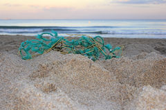 Old Fishing Net on Beach. Worn out green blue rope nylon fishing net jumbled up and washed ashore in front of a sandy atlantic coast beach at sunset emphasizing stock photos