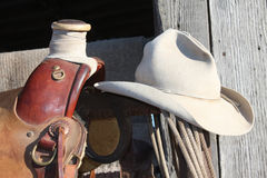 The worn out hat. Old hat on saddle with rope Stock Photography