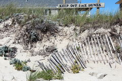 Worn out. Keep off the dunes sign on top of grassy sand dune with  fence in foreground Royalty Free Stock Photography