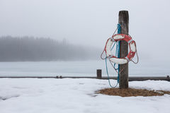 Worn-out lifesaver on post at foggy lake scape. Worn-out lifesaver on a wooden post at foggy lake scape stock images