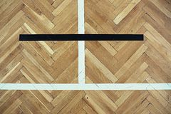 Worn out old wooden floor of sports hall with colorful marking lines. Stock Photos