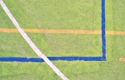 Worn out plastic hairy carpet on outside hanball court. Floor with colorful marking lines. Stock Photo