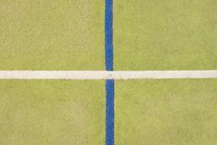 Worn out plastic hairy carpet on outside hanball court. Floor with colorful marking lines. Stock Image