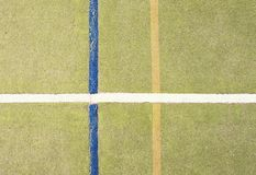 Worn out plastic hairy carpet on outside hanball court. Floor with colorful marking lines. Stock Photography