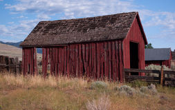 Worn-out red barn. A dilapidated old red barn that is falling apart Stock Photos
