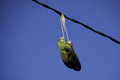 Worn out shoes hanging from a power line Royalty Free Stock Image