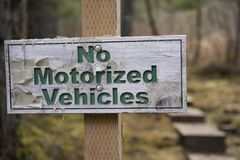 Worn out sign indicating No Motorized Vehicles Stock Image