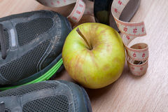 Worn out trainers, dumbbell, tape measure and an apple. Stock Photography