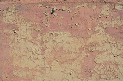 Worn pink peeling paint wall background texture. Royalty Free Stock Image