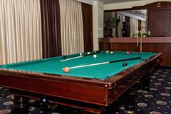 Worn pool table with a cue and balls in the great hall of the gu Royalty Free Stock Photography
