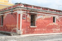 Worn Red Spanish-style house in Antigua Guatemala. Faded red paint covers a low house next to the c cathedral in Antigua Guatemala. The dark red stop sign Royalty Free Stock Images