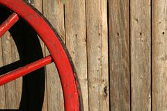Worn Red Wagon Wheel. A worn red wagon wheel leans against a worn wooden backdrop Stock Photography