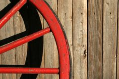 Worn Red Wagon Wheel. A worn red wagon wheel leans against a worn wooden backdrop Stock Photos