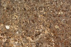 Worn rusty metal surface with partly readable Latin letters Royalty Free Stock Images