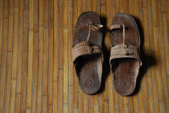 Worn sandal on bamboo mat Royalty Free Stock Images