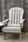 Worn Seating. Old wood patio chair on an outside backyard deck with a weathered wood fence behind it Royalty Free Stock Images