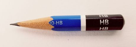 Worn short pencil HB. Very short worn down pencil sharpened HB on a white background or a work desk Stock Images