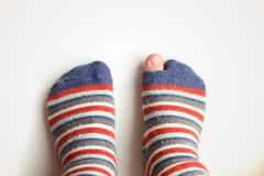 Worn socks with a hole and a finger sticking out of them Royalty Free Stock Images
