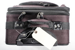 Worn suitcase with tag. A worn well used suitcase with blank tag Royalty Free Stock Photos