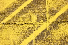 Worn texture with yellow stripes on asphalt Royalty Free Stock Photo