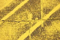 Worn texture with yellow stripes on asphalt Royalty Free Stock Photo