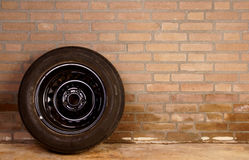Worn tire against the wall Royalty Free Stock Photo