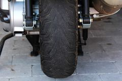 A worn tyre on a motorcycle is dangerous.  Stock Photography