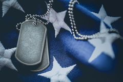 Worn USA military dog tags close up on US American flag with space for text