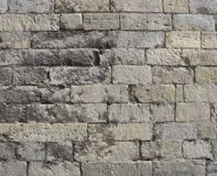 Worn very old large stone wall in gray and beige Stock Photo