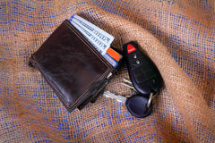 Worn Wallet and Keys. A mans worn wallet with new American hundred dollar bills showing and automobile keys laying on burlap gunny sack background Royalty Free Stock Photography