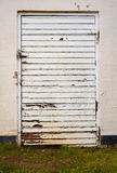Worn Weathered Wooden Door with White Paint Peeling Off. Worn Weathered White Wooden Door with White Paint Peeling Off stock photography