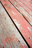 Worn wood planks. Planks of weather-worn wood still partially stained red on a diagonal across frame Royalty Free Stock Photos