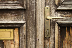 Safety first. Detail of a worn wooden entrance door with a handle Stock Photo