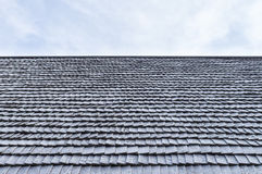 Worn wooden roof shingle of old house. Against sky Royalty Free Stock Photos