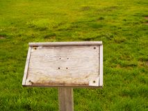 Worn wooden sign in grassy field stock image