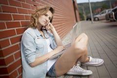 Wornikg trastornado con el ordenador portátil, el thionking del estudiante algo El sentarse al lado de la pared de ladrillo Imagen de archivo libre de regalías