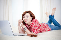 Worreid red haired woman online shopping on white background Stock Image
