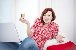 Worreid red haired woman online shopping on white background. Red haired student business woman wearing a red shirt worried after online shopping on white Royalty Free Stock Image