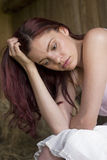 Worried. Beautiful young woman sitting in a sunlit barn looking worried Royalty Free Stock Images