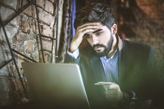 Worried about account. Too much money I spend this month. Young businessman sitting and using laptop Royalty Free Stock Image