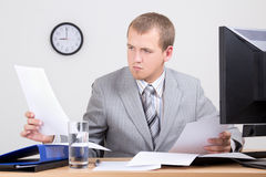 Worried accountant doing paperwork in office Royalty Free Stock Image